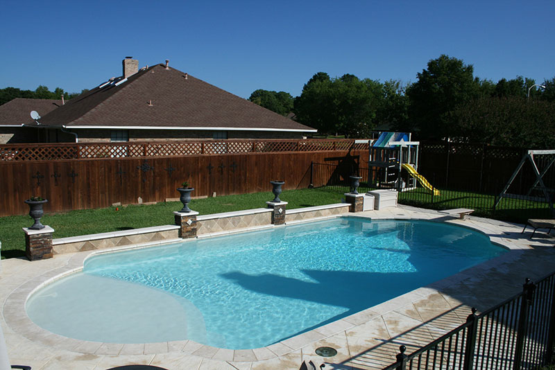 This Highland Village Texas diving pool features; a multi-level raised wall with stone columns, travertine cap, travertine tile veneer, sheer descent waterfall, a large tanning ledge, travertine coping, stamped concrete decking and a superblue aggregate finish interior.