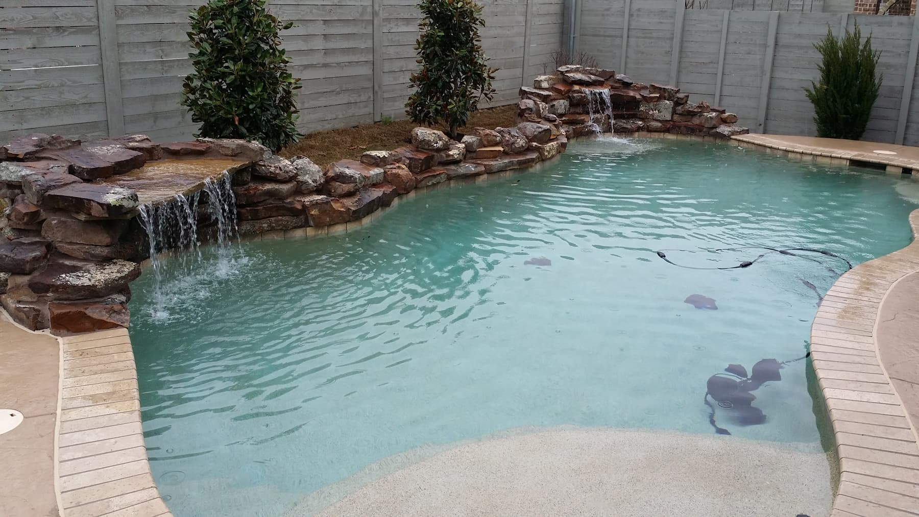 Dueling natural stone waterfalls welcome you to the sky blue waters defined by the alternative brick coping in this Justin area swimming pool.