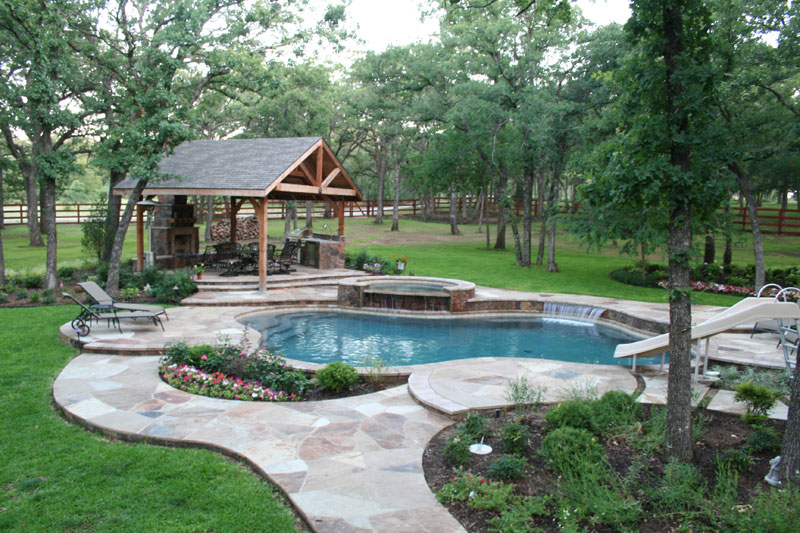 Stone decking, tumbled travertine, water slide and arbor with an outdoor kitchen accentuate this elevated pool/spa project. The 4' stainless steel sheer descent waterfall emerges from the Oklahoma veneered raised beam spilling into the dark blue pebble finish of this Argyle area environment.