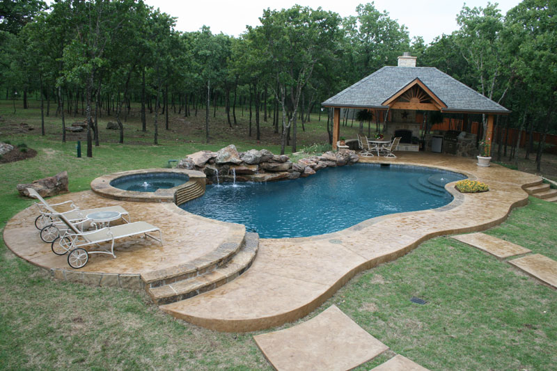 Carved into this Argyle Texas hillside as if its soul beginning purpose was to end there sits this waterfall enriched residential swimming pool. The moss boulder waterfall extends from the elevated spa to the arbor enclosed outdoor kitchen. Stamped concrete decking lends access to the Oklahoma coping of the Midnight blue pebblesheen finish swimming pool.