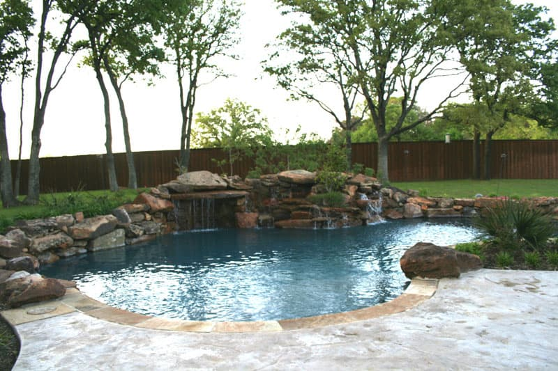 The massive boulders of the waterfalls encompass a planter bed next to the grotto of this Denton, Texas Swimming pool. Stamped concrete decking gives way to Oklahoma Coping which leads you to the midnight blue pebble finish of this backyard Oasis.