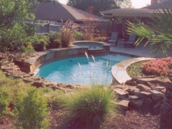 A moss boulder waterfall serves as the backdrop for this South Denton, Texas swimming pool. A Tahoe blue aggregate pool surface accentuates the Oklahoma flagstone used as coping and veneer for the raised beam and the elevated spa as it protrudes from the hillside into the washed aggregate decking.