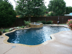 Colorful landscaping lend to the natural setting of this deep blue pebble finish Denton Texas swimming pool, accented in Oklahoma flagstone coping and engulfed in washed aggregate decking.