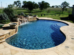 Stamped concrete decking, travertine coping, a random Oklahoma veneered raised beam and yet the vantage point of this Pilot Point swimming pool is a large grotto with stone pots spilling into the midnight blue aggregate finish.