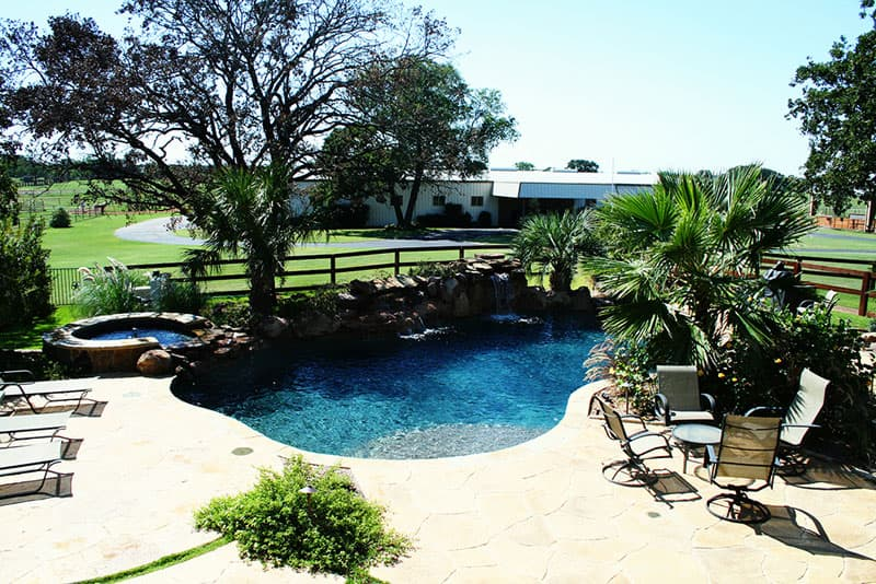 This Argyle, Texas swimming pool was designed with a rustic style in mind; moss rock boulders waterfalls, Oklahoma flagstone, stamped concrete decking, midnight blue pebble finish interior, large tanning ledge and elevated spa are used to achieve this look.
