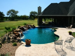 This Argyle, Texas swimming pool was designed with a rustic style in mind; moss rock boulders waterfalls, Tumbled travertine coping, stamped concrete decking, midnight blue pebble finish interior, large tanning ledge and elevated spa are used to achieve this look.