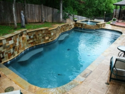 The hand cut Oklahoma veneer on the multi-level raised beam blend into the elevated spa as it spills into the Tahoe blue aggregate finish of this Corinth, Texas swimming pool. The Oklahoma flagstone coping and pattern stamped concrete decking complete the design.