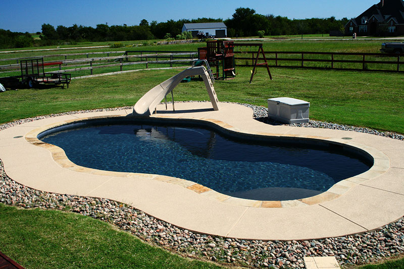 This midnight blue aggregate finish interior swimming pool features; a turbo twister slide, Oklahoma coping, buff spray-deck and matching waterline tile.